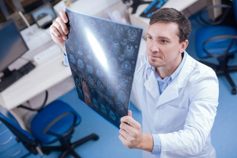 Oncologiste professionnel bel regardant les images de rayon du cerveau X photo libre de droits