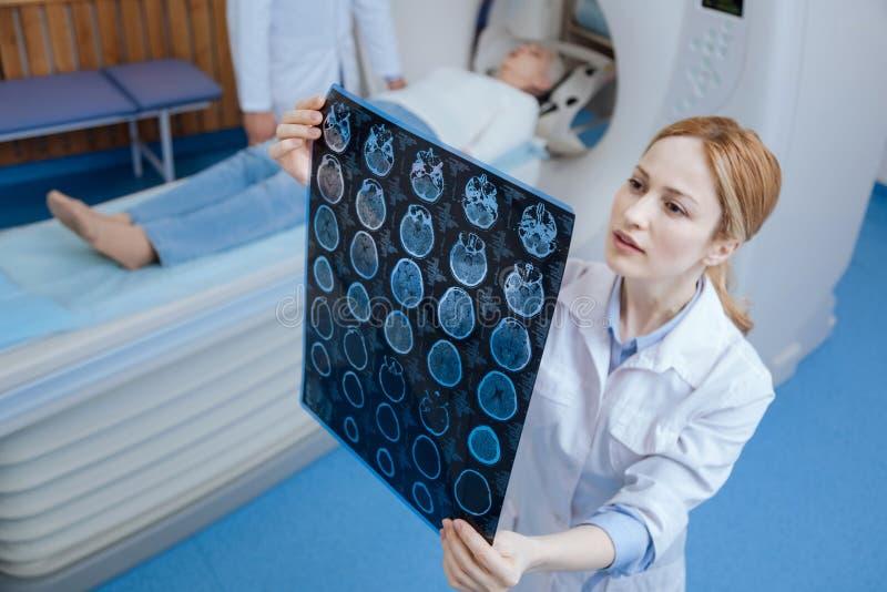 Oncologiste professionnel expérimenté regardant les résultats de balayage d'IRM photos stock