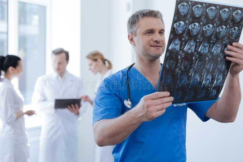Oncologiste réfléchi analysant la photo de balayage de ct dans la clinique photos stock
