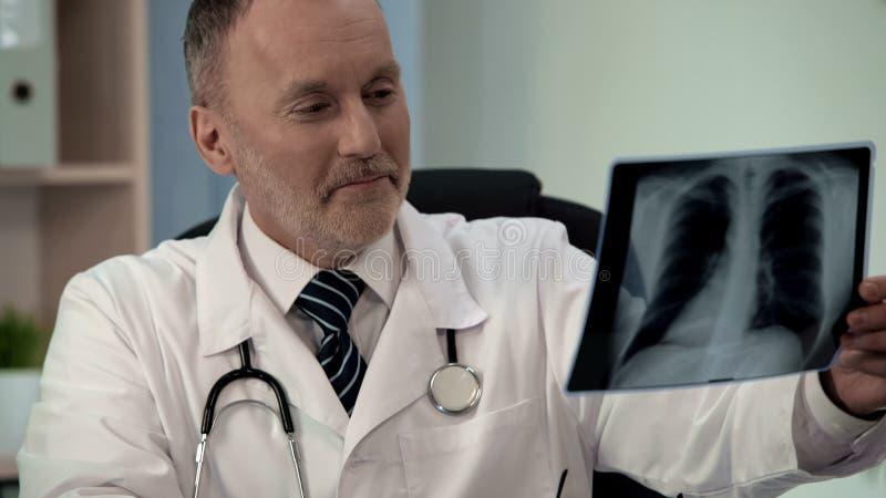 Oncologiste voyant le rayon X et se réjouissant au rétablissement merveilleux de patients du cancer photo stock