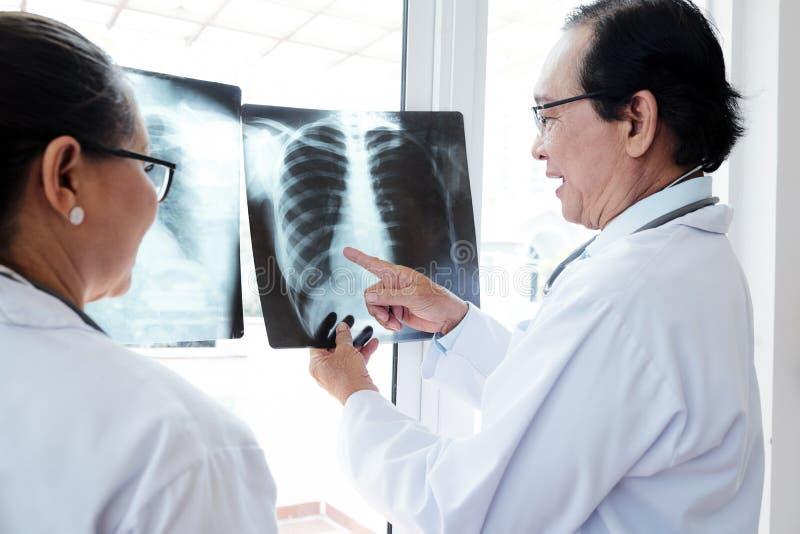 Oncologistes discutant la radiographie de la poitrine photos libres de droits