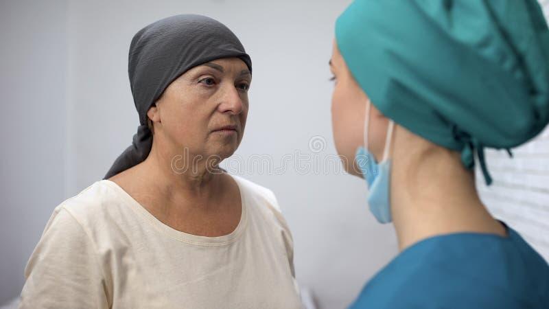 Oncologo che informa paziente disperato circa le metastasi, concetto di consapevolezza del cancro fotografia stock libera da diritti