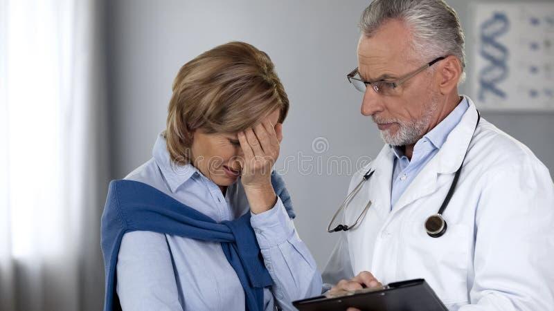 Oncologo che informa signora turbata circa i cattivi risultati dei test, trattamento del cancro fotografia stock libera da diritti