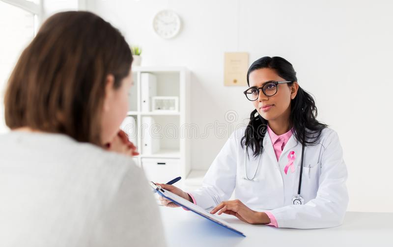 Doctor with pink awareness ribbon and patient. Oncology and breast cancer concept - female doctor with pink awareness ribbon and patient at hospital royalty free stock photography