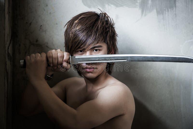 Ond asiatisk man med svärdet av rättvisa arkivfoto