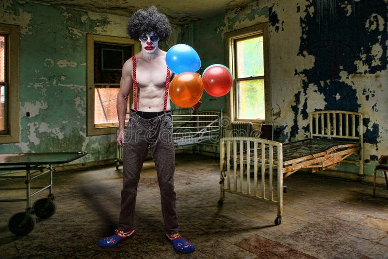 Ond clown Inside Condemned Room med sjukhussäng royaltyfria bilder
