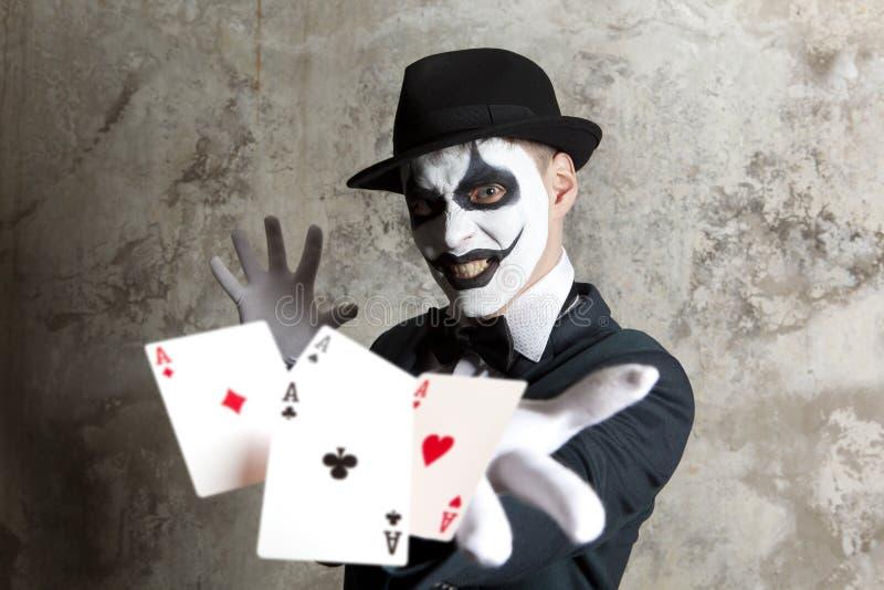 Ond clown som spelar med pokerkort royaltyfria foton