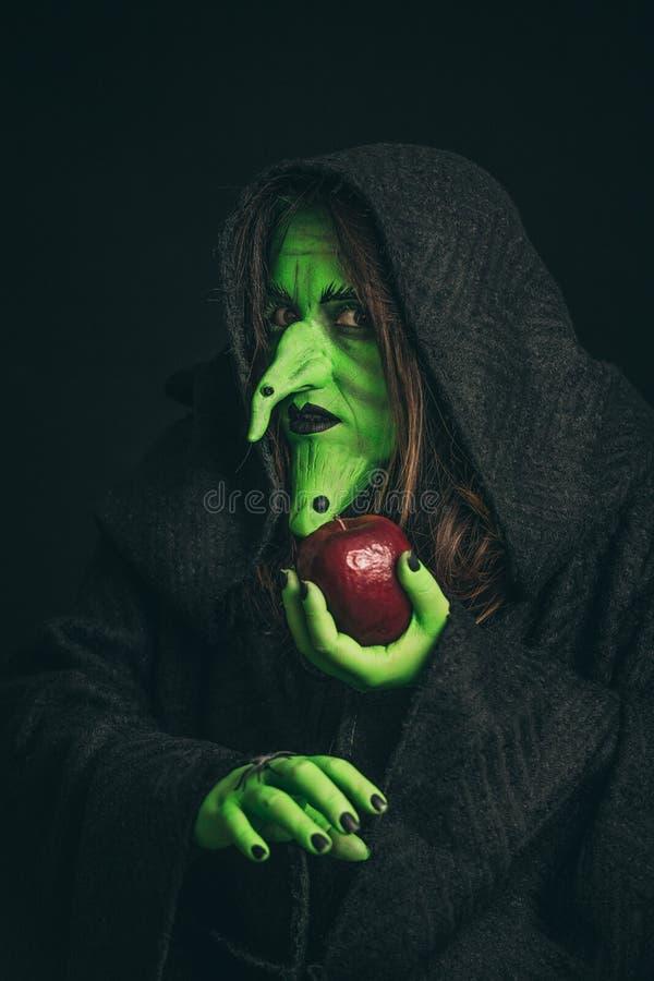 Ond häxa med ett ruttet äpple och en spindel på henne händer arkivfoto