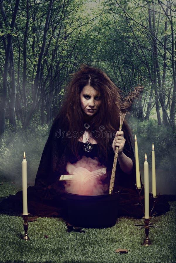 Ond häxa som rör hennes magiska dryck i en kittel royaltyfria foton