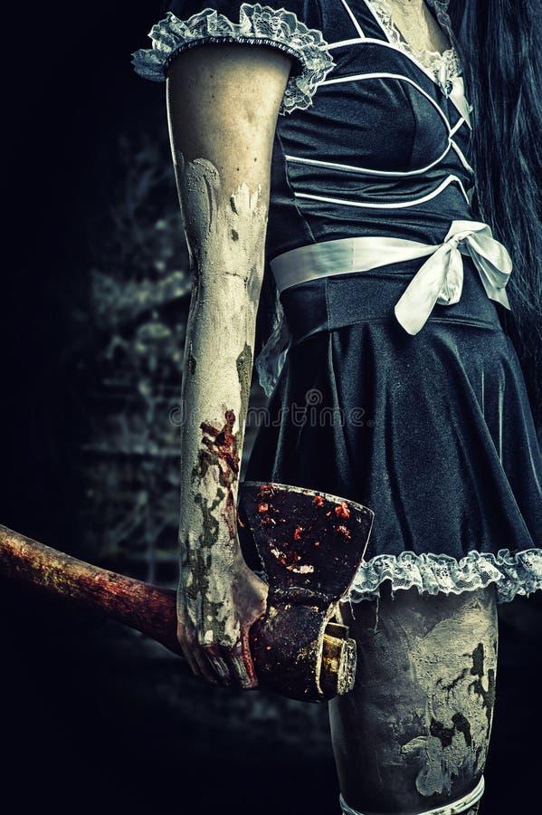 Ond kvinna som rymmer en blodig yxa arkivbilder