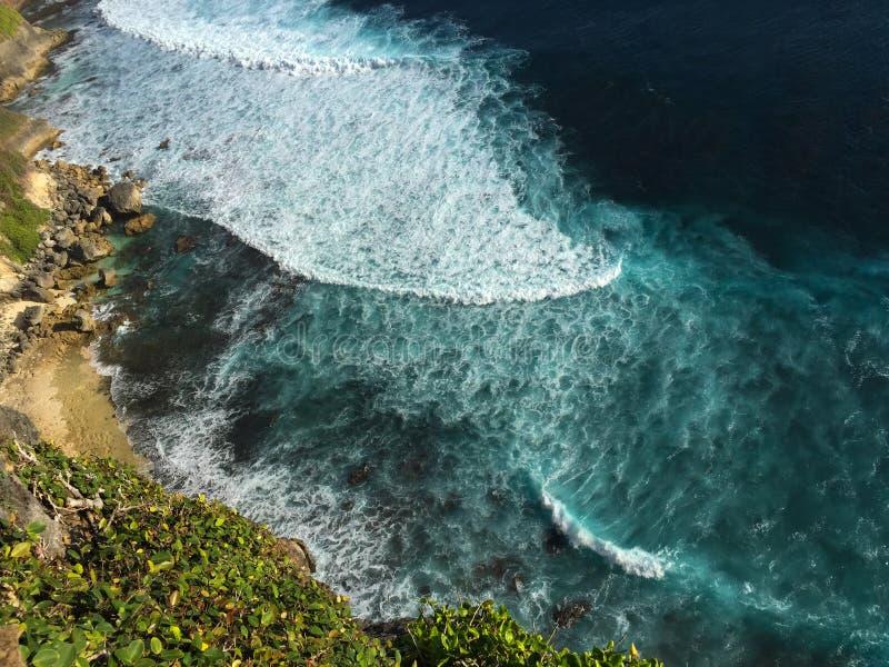 A onda azul da onda do rasgo do oceano espirra na praia amarela da areia Perigo tropical do mar fotografia de stock