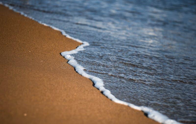 Onda blanca del mar en el primer de oro de la arena playa Agua azul Marea del mar imagen de archivo libre de regalías