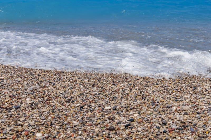 Onda blu e spiaggia dell'acqua di mare vicine su con le bolle fotografie stock libere da diritti