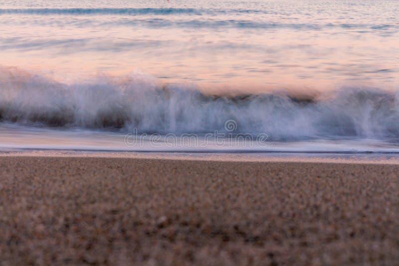 onda blured Cores do nascer do sol refletidas na água do mar fotos de stock royalty free