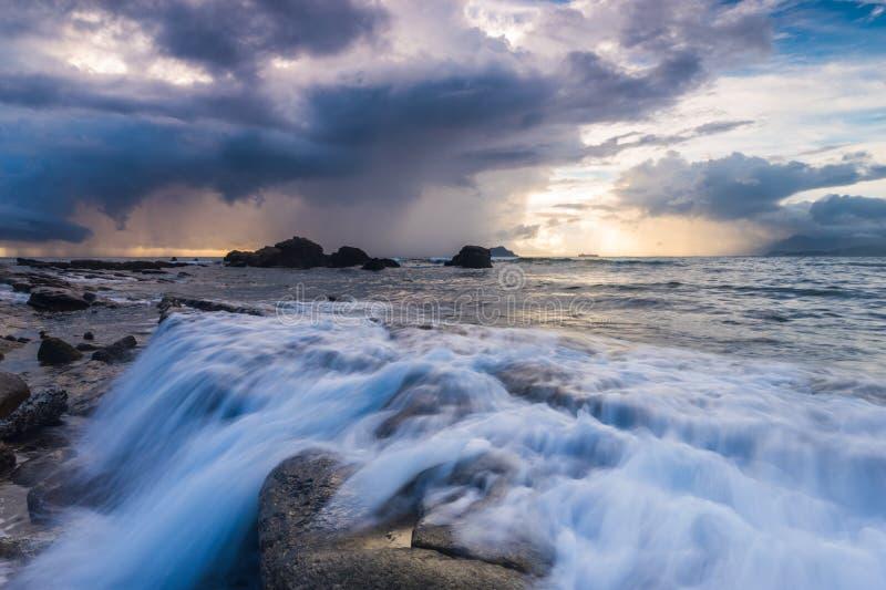 Onda branca e o nascer do sol rochoso do litoral foto de stock royalty free