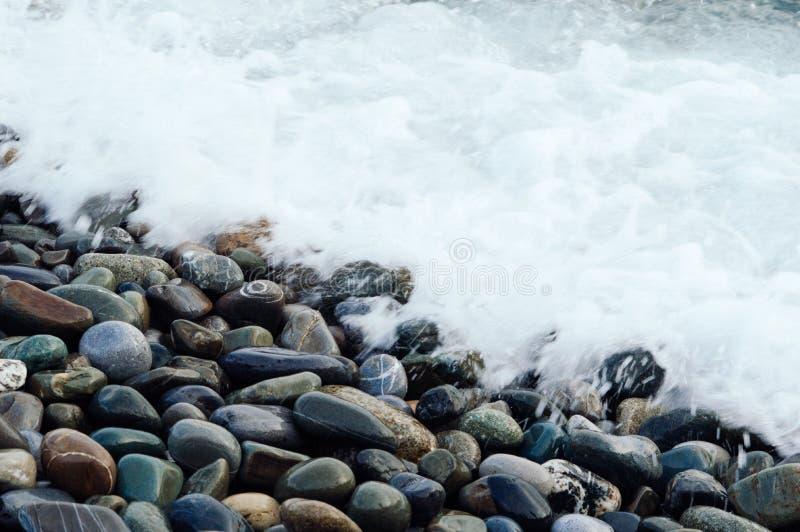 Onda branca que lava as pedras da costa Fundo com a praia da pedra fotos de stock