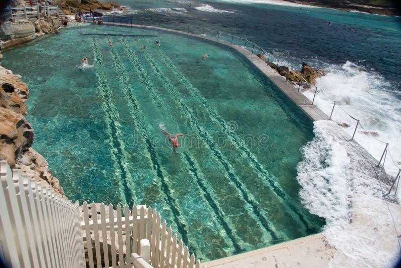 Onda che colpisce un raggruppamento naturale con i nuotatori fotografia stock libera da diritti