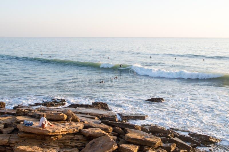 Onda da equitação do surfista em panoramas no taghazout quando dois outro remarem para fora fotos de stock