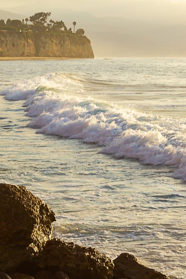 Onda de formação de espuma que quebra no espanse do oceano com penhasco e pedregulhos imagem de stock