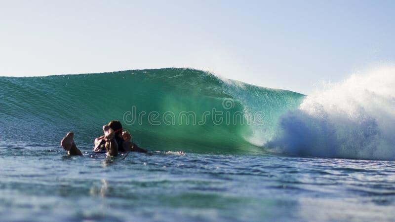 Onda degli orologi del surfista che si rompe dall'acqua fotografie stock libere da diritti