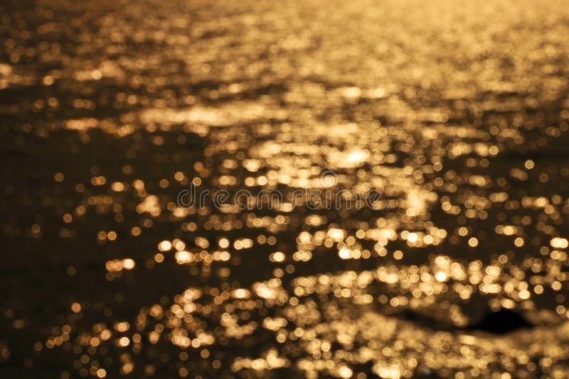 Onda del mar de la resaca de Blured en el fondo ligero de oro de la playa de la puesta del sol foto de archivo