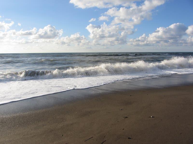 Onda del mar en la playa de la arena Della Pescaia, provincia de Castiglione de Grosseto, Italia foto de archivo