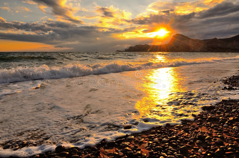 Onda del mare sulla spiaggia, la spuma sulla costa di Mar Nero al tramonto immagini stock