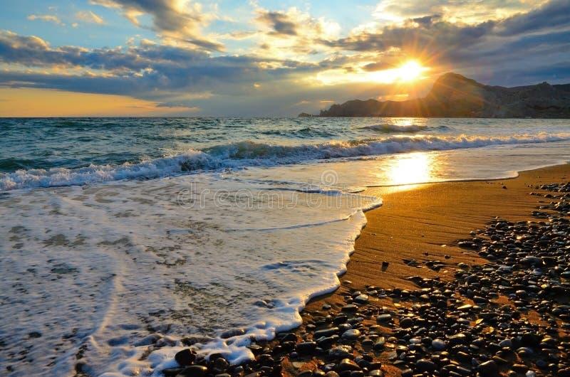 Onda del mare sulla spiaggia, la spuma sulla costa di Mar Nero al tramonto fotografie stock