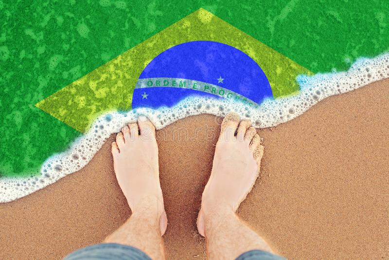 Onda del mare sulla spiaggia sabbiosa soleggiata con la bandiera Brasile Vista superiore sui piedi nella sabbia fotografia stock