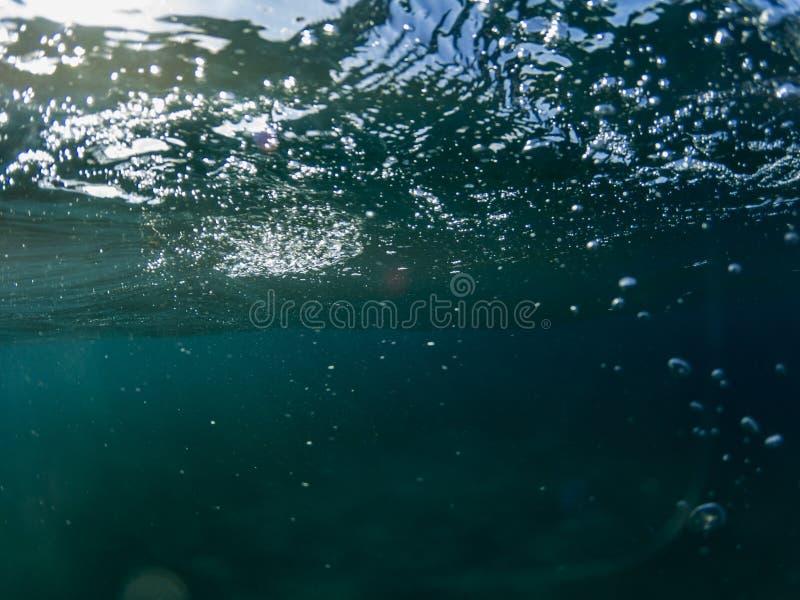 Onda dell'acqua di mare con la foto subacquea del primo piano delle bolle Superficie blu del mare da sotto Ondulazioni sulla supe fotografia stock libera da diritti