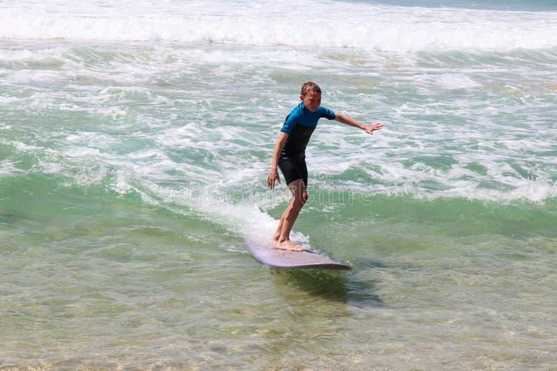 Onda di guida del ragazzo sul longboard porpora alla spiaggia fotografia stock libera da diritti