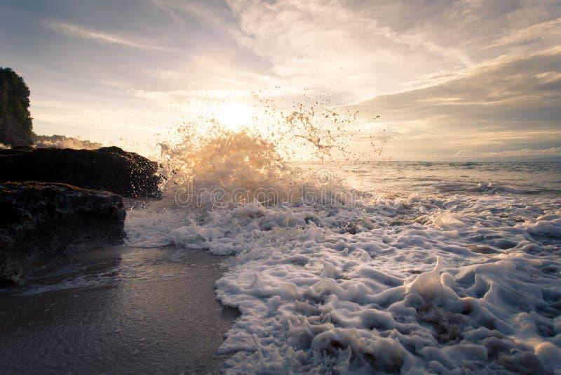Onda di oceano con la battitura della schiuma contro le rocce al tramonto fotografie stock libere da diritti