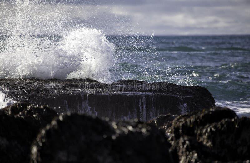 Onda di oceano profondo che si schianta sulle rocce fotografie stock libere da diritti