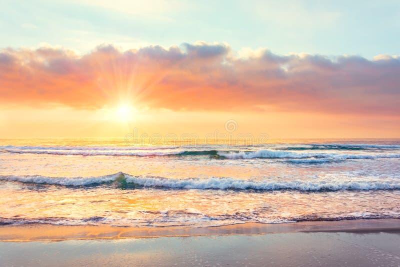 Onda di oceano sulla spiaggia a tempo di tramonto, raggi del sole fotografia stock