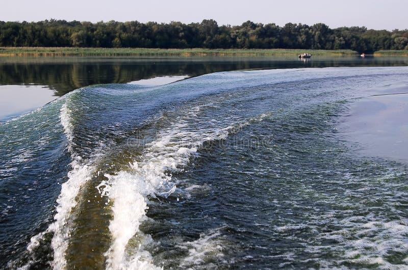 Onda do Fishtail e banco do rio atrás do barco inflável do motor foto de stock