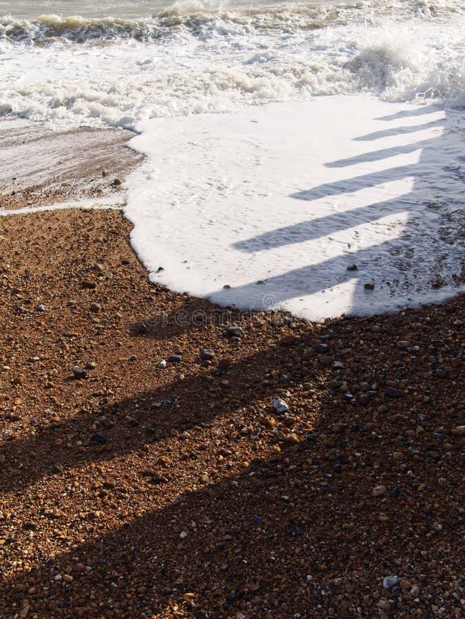 Onda do mar na praia da areia Sombras dos disjuntores de onda que moldam na superfície da praia e da água imagem de stock