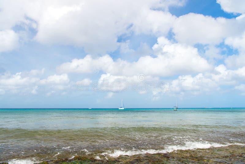 Onda do mar, praia e céu nebuloso azul Água da natureza, oceano, paisagem do verão O curso, relaxa férias Ilha ou costa tropical  imagens de stock