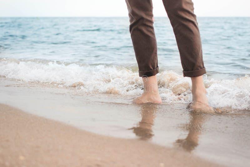 Onda do mar que deixa de funcionar nos pés do homem imagens de stock royalty free