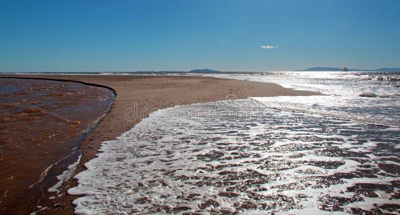 Onda en el banco de arena donde el Océano Pacífico y la reunión del río Santa Clara en la playa de la loma de las personas que pr fotos de archivo