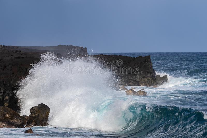 Onda en la playa negra de la arena, isla grande, Hawaii Acantilados volcánicos en fondo fotografía de archivo