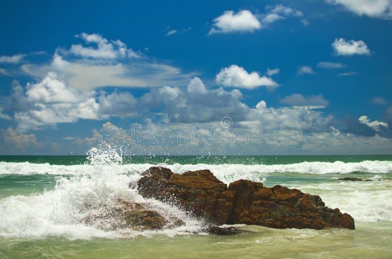 A onda está quebrando da rocha na praia com céu azul e a nuvem branca imagem de stock