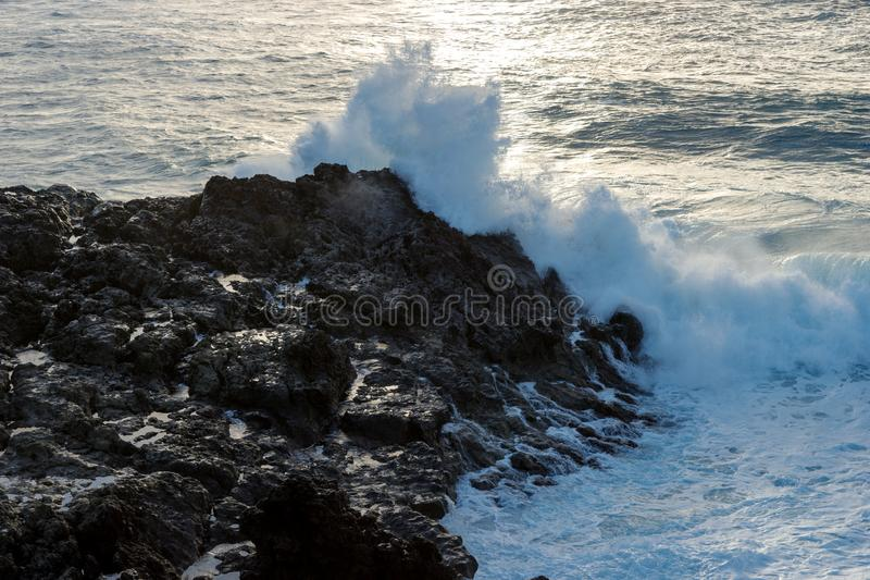 A onda forte encontra rochas da lava na costa foto de stock