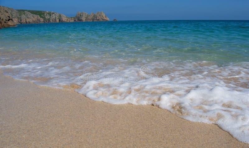 Onda hecha espuma en la playa arenosa del porthcurno, agua pura del mar céltico, verano en Cornualles, West End del sur, Reino Un foto de archivo libre de regalías