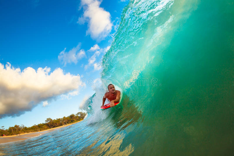 Onda praticante il surfing di tramonto fotografia stock