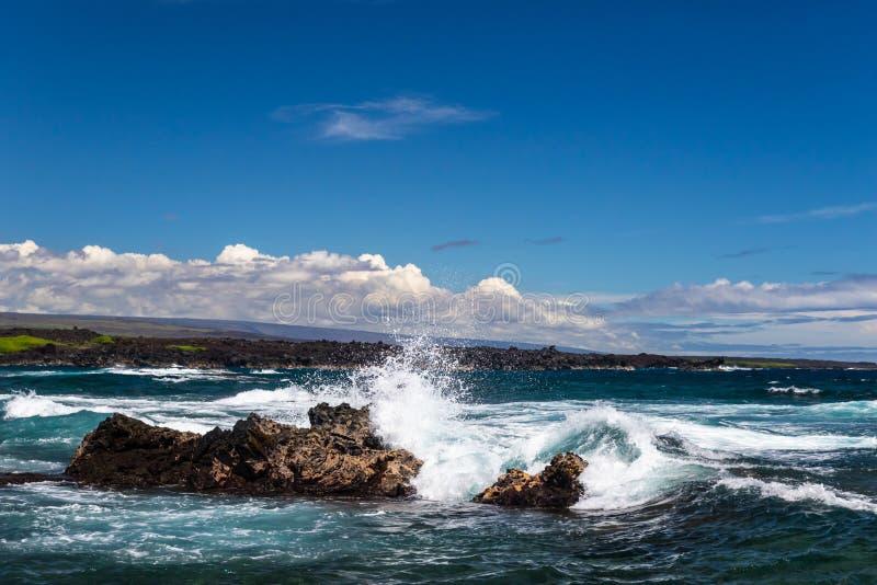 Onda que deixa de funcionar na rocha escura da lava; pulverizador branco no ar; litoral, oceano e nuvens no fundo Praia preta da  fotos de stock