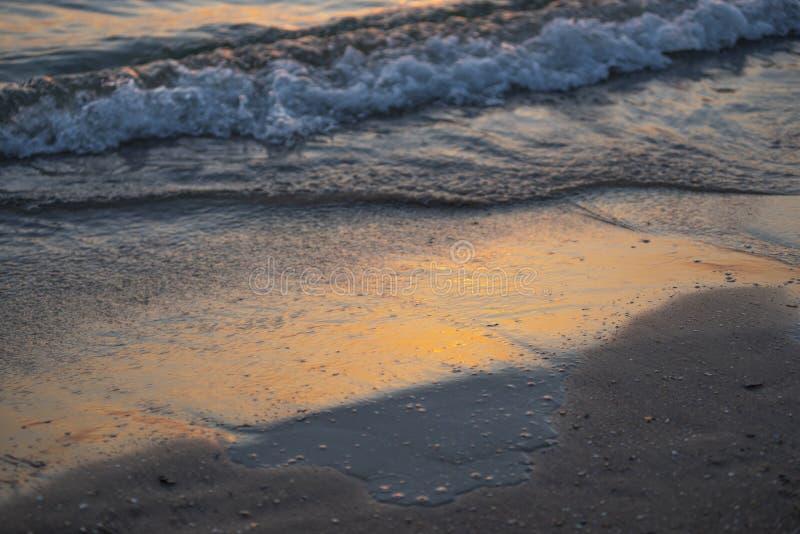 Onda que practica surf del océano hermoso en la playa de la puesta del sol imagenes de archivo