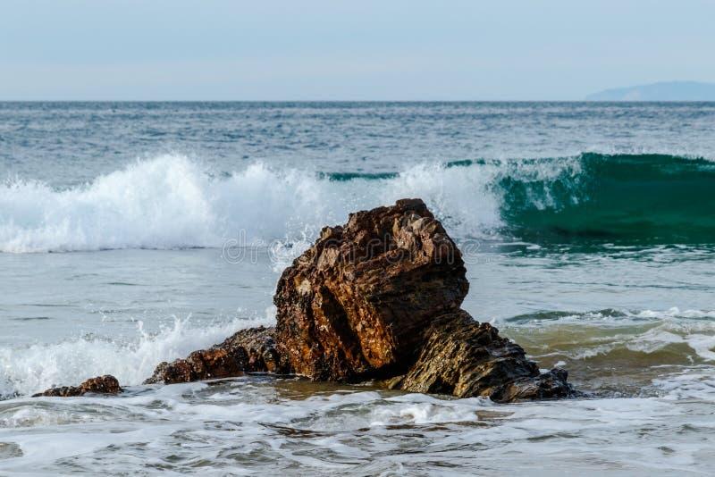 Onda que quebra atrás da rocha perto da costa pacífica; espuma no primeiro plano, céu no fundo imagens de stock royalty free