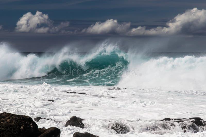 Onda que quebra na costa ocidental de Kona em Havaí Pulverizador e espuma brancos na água Rochas no primeiro plano fotografia de stock royalty free
