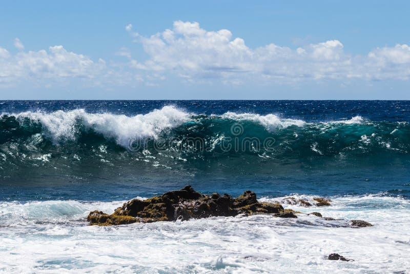 Onda que quebra no mar em Havaí; rocha vulcânica e espuma no primeiro plano Oceano azul, céu, nuvens no fundo imagem de stock