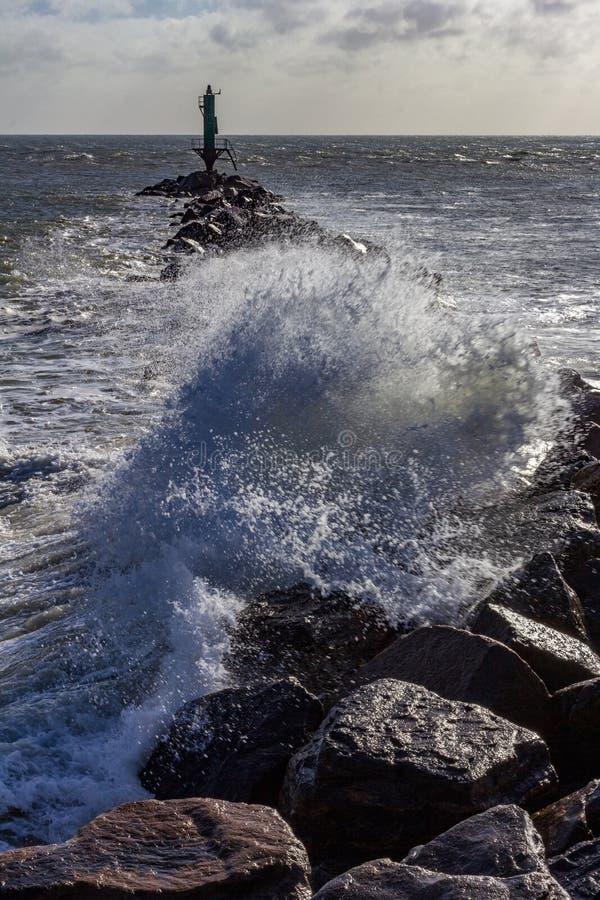 Onda que se estrella sobre un embarcadero Ramsgate, Inglaterra de la roca fotografía de archivo